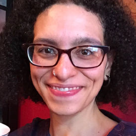 The photo depicts author Emily August, an assistant professor of literature at Stockton University. She is smiling and wearing glasses.