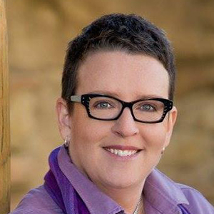 Image depicts award-winning romance author Kimberly Cooper Griffin. She is wearing glasses and smiling.